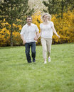 Couple running through park holding hands Stock Photo