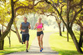Couple running in park jogging outside the at sunrise on beatiful path healthy lifestyle fitness concept Stock Photos