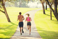 Couple running in park jogging outside the at sunrise on beautiful path healthy lifestyle fitness concept Stock Photos