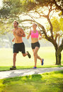 Couple running in park jogging outside the at sunrise on beautiful path healthy lifestyle fitness concept Royalty Free Stock Photography