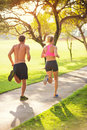 Couple running in park jogging outside the at sunrise on beautiful path healthy lifestyle fitness concept Stock Photo