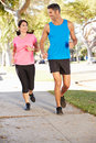 Couple running on suburban street towards camera Royalty Free Stock Image