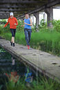 Couple running training caucasian men and women in industrial nature environment Stock Photography