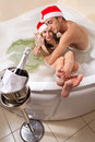 Couple in santa hats is enjoying a bath Royalty Free Stock Photo