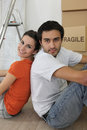 Couple sat by ladder and boxes Royalty Free Stock Images