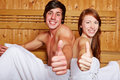 Couple in sauna holding thumbs up Stock Photo