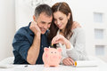 Couple saving money portrait of happy inserting coin in piggybank Royalty Free Stock Images