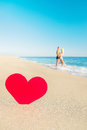 Couple at sea beach and big red heart st valentines day conce lovers embrace concept Stock Photography