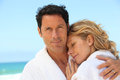 Couple by the sea in matching bathing robes Royalty Free Stock Image