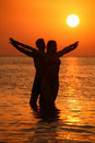 Couple in sea on sunset with hands as wings Stock Photos