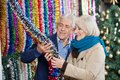 Couple selecting tinsels at store senior christmas Stock Photo