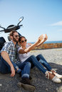 Couple selfie taken near the ocean happy sitting against their scooter taking a on holiday Royalty Free Stock Photos