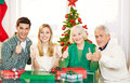 Couple and senior people holding thumbs up at christmas with gifts Royalty Free Stock Photos