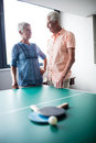 Couple of seniors interacting behind a ping pong table in the retirement house Royalty Free Stock Image