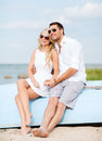 Couple in shades at sea side summer holidays and dating concept sitting Royalty Free Stock Images