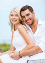 Couple in shades at sea side summer holidays and dating concept sitting Royalty Free Stock Photo