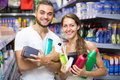 Couple with shampoo in the store smiling good spirits detergents and perfume Royalty Free Stock Images