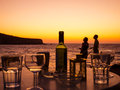 Couple sharing a romantic sunset after an evening drinking wine in silhouette Stock Images