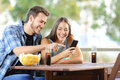 Couple sharing a smart phone outdoors sitting on hotel or home terrace Royalty Free Stock Photography