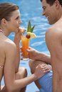Couple sharing tropical drink at poolside Royalty Free Stock Photo