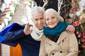 Couple with shopping bags at christmas store portrait of happy senior standing Stock Images
