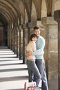 Couple with shopping bags embracing side view of a under archway Royalty Free Stock Photography
