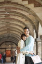 Couple with shopping bags embracing side view of a under archway Royalty Free Stock Images