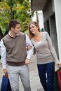 Couple with shopping bags happy young walking together on pavement Royalty Free Stock Images