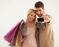 Couple with shopping bags making a self portrait smiling caucasian holding mobile phone Royalty Free Stock Photos