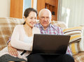 Couple shopping at home via internet middle aged men and women sitting on couch with laptop Royalty Free Stock Images