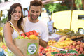 Couple shopping at open street market carrying a paper bag with a organic certified label full of fruit and vegetables Stock Photography