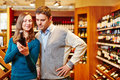 Couple shopping for wine in beverage market bottle of red a Stock Photos