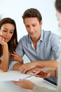 Couple signing contract with real estate agent future property owners reading terms of Stock Photography