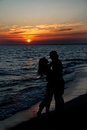 Couple silhouette on beach against sunset Royalty Free Stock Photography