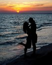 Couple silhouette on beach against sunset Royalty Free Stock Photo