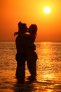 Couple silhouette embraces and kisses on sunset Stock Image