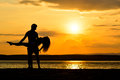 Couple silhouettes holding at sunset by the sea, dancing Royalty Free Stock Photo