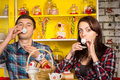 Couple sipping a drink from small cups at the cafe close up young white in casual outfits doing pose white while looking camera Royalty Free Stock Photography