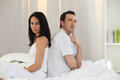 Couple sitting back to back on the bed Stock Photography