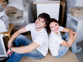 Couple sitting back-to-back after moving Royalty Free Stock Photo
