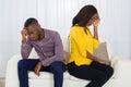 Couple Sitting Back To Back On Sofa