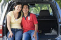 Couple sitting in back of van smiling Stock Image