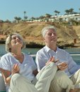 Couple sitting on beach happy older meditating Stock Photo