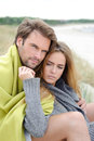Couple sitting on the beach under blanket relaxing and enjoying themselves beautiful time of a year windy sunny day love in air Stock Photo