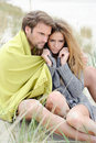 Couple sitting on the beach under blanket relaxing and enjoying themselves beautiful time of a year windy sunny day love in air Royalty Free Stock Images