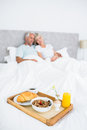 Couple sitting on bed with breakfast in foreground blurred mature at home Royalty Free Stock Photos
