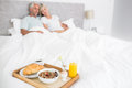 Couple sitting on bed with breakfast in foreground blurred mature at home Stock Photo