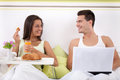 Couple sitting on bed in morning young and smiling women having breakfast and men using laptop Royalty Free Stock Images