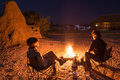 Couple sitting at burning camp fire in the night. Camping in the desert with wild elephants in background. Summer adventures and e Royalty Free Stock Photo