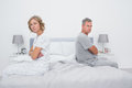 Couple sitting on different sides of bed not talking after argum argument looking at camera in bedroom at home Royalty Free Stock Image